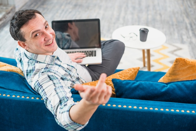 Cheerful man sitting on couch with laptop Free Photo