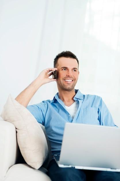 Uomo allegro che utilizza computer portatile e che parla sul telefono cellulare Foto Gratuite