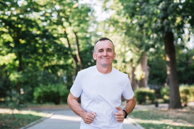 Cheerful man in white tshirt running in a park Free Photo