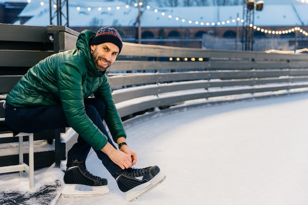 Cheerful man with appealing appearance laces up skates, sitts on ice arena, wants to go skating with friends Premium Photo