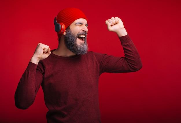 ひげの彼のワイヤレスヘッドフォンで音楽を聴くと陽気な男 Premium写真