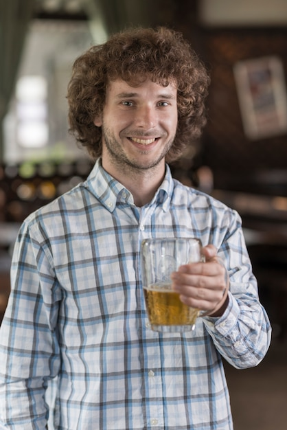 Cheerful man with beer in bar Free Photo