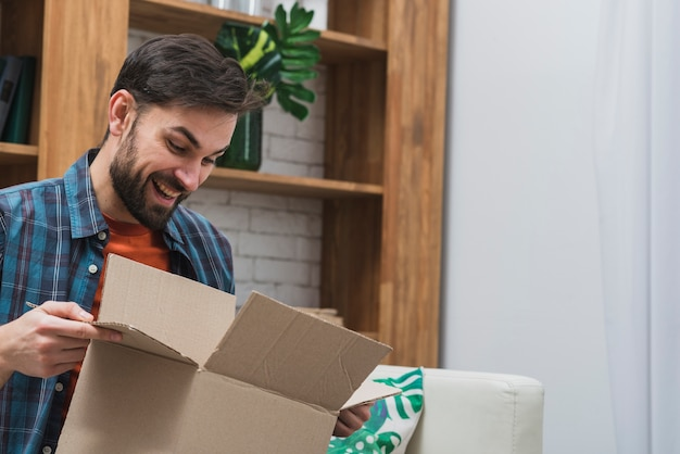 Cheerful man with opened parcel Free Photo