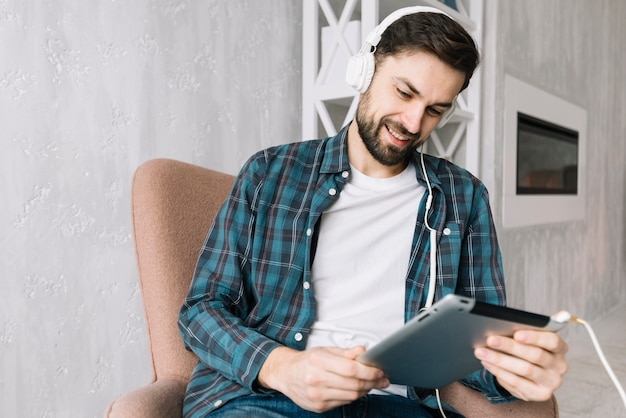 Cheerful man with tablet listening to music Free Photo