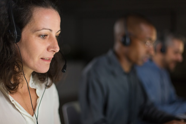 Cheerful mature call center operator looking at laptop screen Free Photo