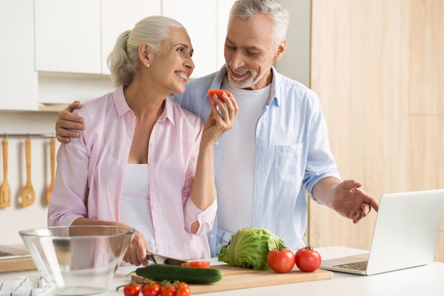 Cheerful mature loving couple family using laptop and cooking Free Photo