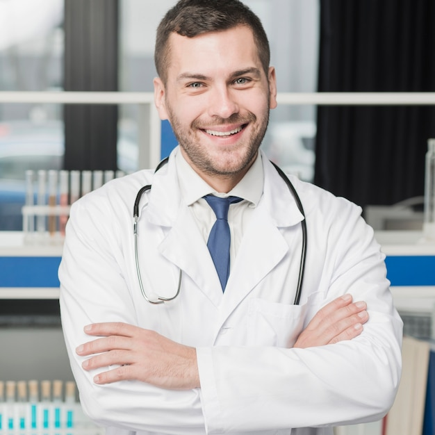 Cheerful medic standing with arms crossed Free Photo