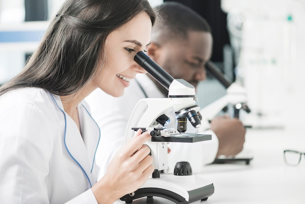 Cheerful medic woman looking at microscope Free Photo