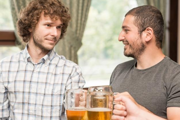 Cheerful men clinkingmugs in bar Free Photo