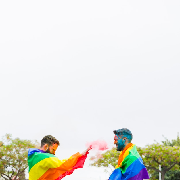 Cheerful men in rainbow flags throwing powder paint on street Free Photo