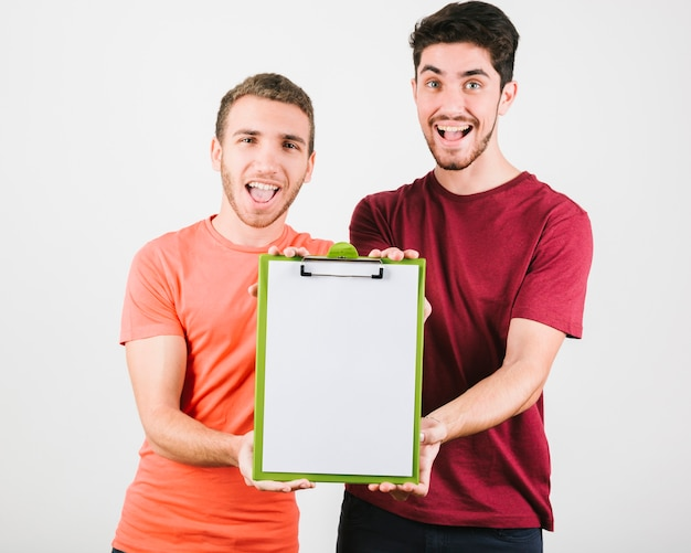 Cheerful men showing tablet with paper to camera Free Photo