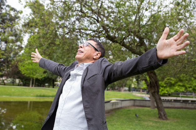 Cheerful middle-aged man spreading hands in park Free Photo