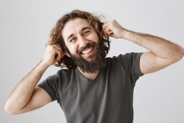 陽気な中東の男が遊び心のある耳を引っ張る、誰かをからかう 無料写真