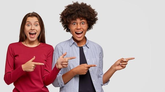 쾌활한 혼혈 소녀는 재미 있고 즐거운 표정을 지으며 밀접하게 서서 빈 복사본 공간에서 두 검지 손가락으로 옆으로 표시 멋진 장소를 광고합니다. 다문화 판매자 무료 사진