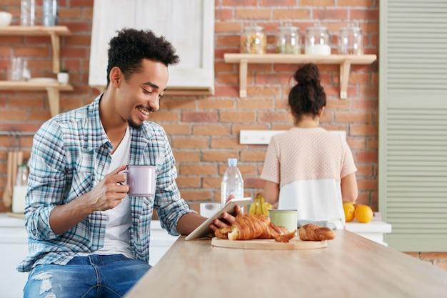 Allegro maschio di razza mista guarda la commedia su tablet, utilizza la connessione internet gratuita, beve caffè Foto Gratuite