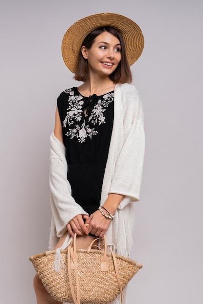 Веселая современная брюнетка женщина в летней одежде бохо и позирует в соломенной шляпе. Бесплатные Фотографии