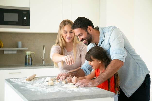 陽気なママとパパが小麦粉を乱雑にキッチンテーブルに生地を作るように娘を教えています。若いカップルと彼らの女の子が一緒にパンやパイを焼きます。家族の料理のコンセプト 無料写真