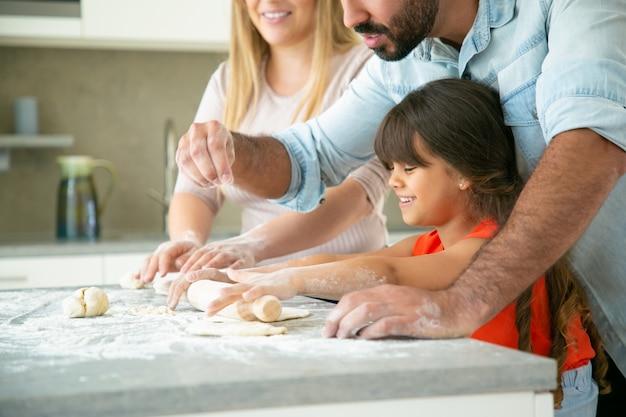 Веселая мама и папа учат счастливую дочь раскатывать тесто на кухонном столе с грязной мукой. молодая пара и их девочка вместе выпекают булочки или пироги. концепция семейной кухни Бесплатные Фотографии