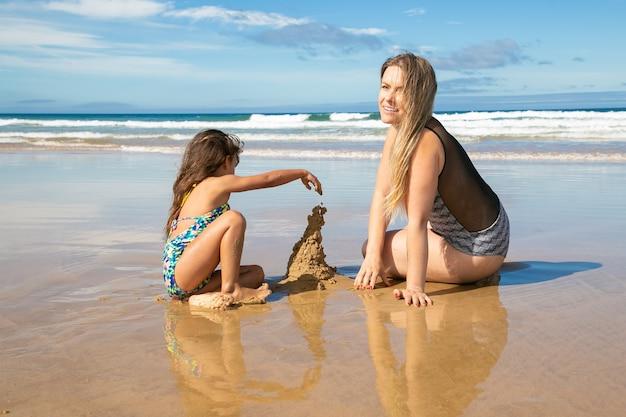 陽気なお母さんと小さな娘がビーチで砂の城を建て、濡れた砂の上に座って、海での休暇を楽しんでいます 無料写真