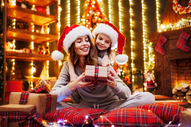 Cheerful mom and her cute daughter girl exchanging gifts. parent and little children having fun near tree indoors. loving family with presents in christmas room. Premium Photo