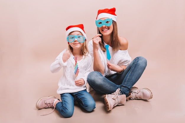 Mamma allegra e sua figlia felice carina in maschere di carnevale e cappelli di babbo natale Foto Gratuite