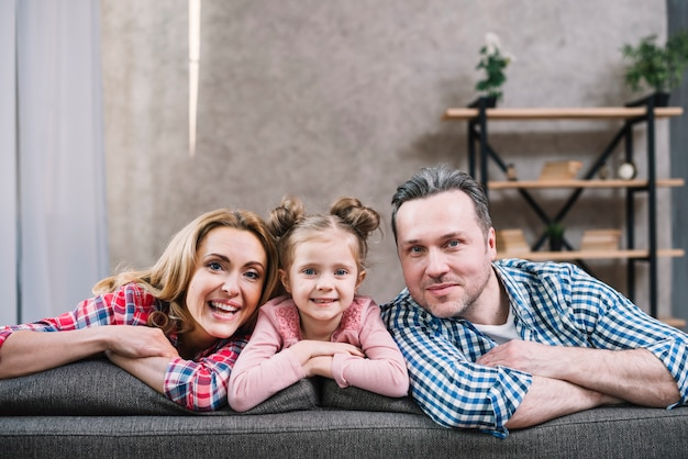 Cheerful mother; daughter and father sitting on sofa looking at camera Free Photo