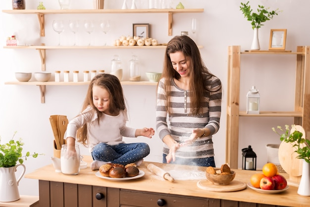 Cheerful mother and daughter in the kitchen preparing breakfast. knead the dough from flour for pancakes, cookies and rolls. flies flour and all laugh Premium Photo