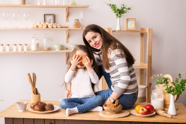 Cheerful mother and daughter in the kitchen preparing breakfast. they eat cookies, play pancakes and laugh Premium Photo