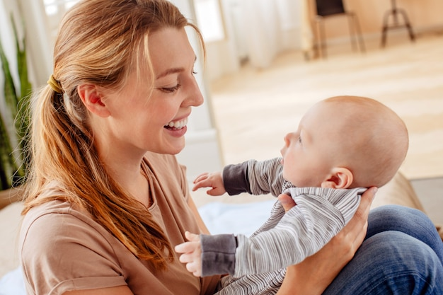 Cheerful mother holding infant at home Premium Photo