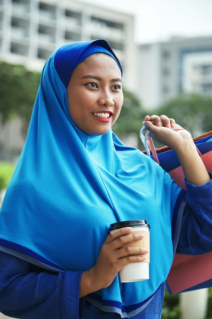 Cheerful muslim female with hot beverage after shopping Free Photo