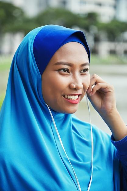 Cheerful muslim woman in earphones Free Photo