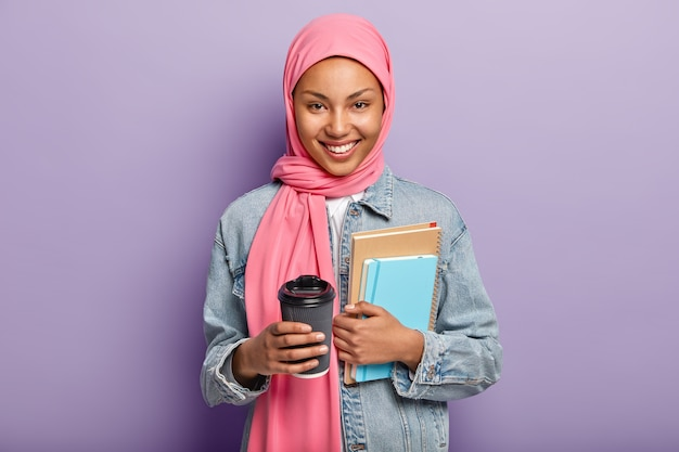 Cheerful muslim woman in pink hijab, denim coat, carries pocketbook Free Photo