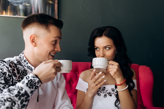 Cheerful newlyweds rest on a bright pink sofa in the cafe Free Photo