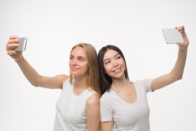 Cheerful and nice young woman stand back to back and take selfies Premium Photo