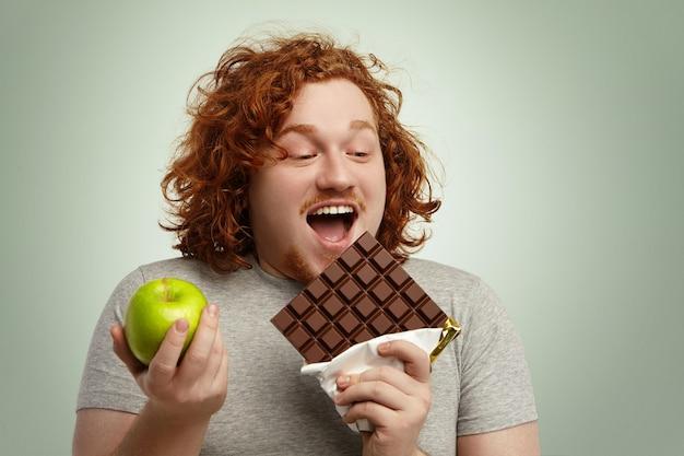 Веселый тучный мужчина широко открывает рот, держа в одной руке большую плитку шоколада, а в другой - зеленое яблоко Бесплатные Фотографии