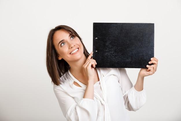 Веселая офисная леди показывает баннер на черном буфере обмена Бесплатные Фотографии