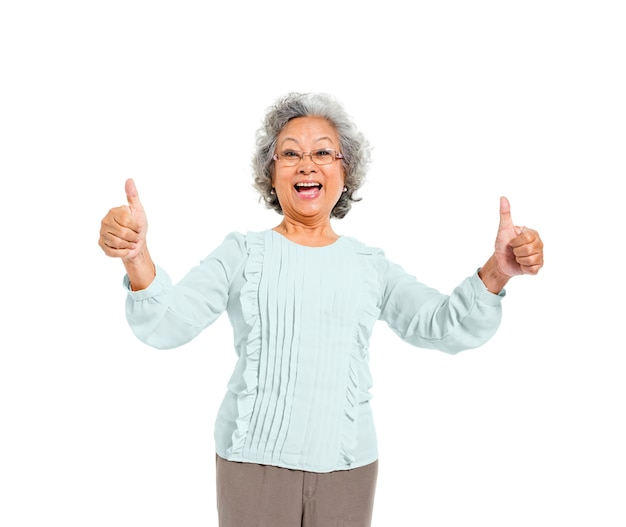A cheerful old casual woman giving a thumbs up Free Photo