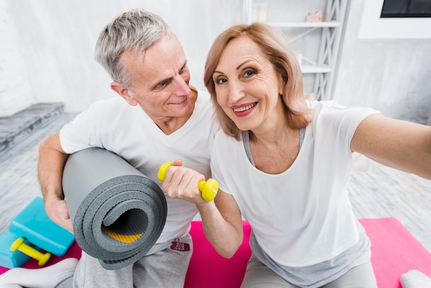 Cheerful old couple taking self portrait holding yoga mat and dumbbells in hand Free Photo