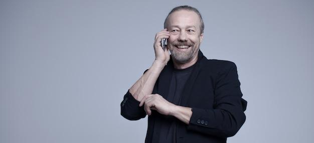 Cheerful old man talking on the phone. Premium Photo