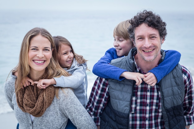 Cheerful parents carrying children on back at beach Premium Photo