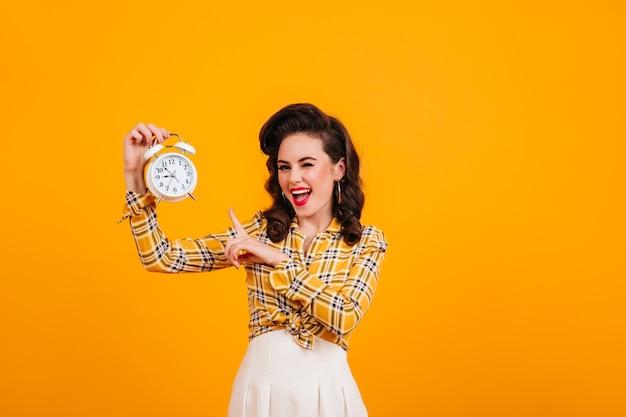 Ragazza allegra del pinup che mostra orologio. studio shot di beata donna attraente isolata su sfondo giallo. Foto Gratuite