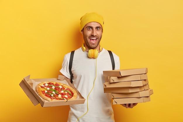 Веселый доставщик пиццы стоит с картонными коробками, ждет клиента, носит желтую шляпу и белую футболку, слушает музыку во время транспортировки фаст-фуда Бесплатные Фотографии