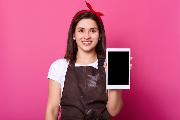 Веселая приятная брюнетка стоит и дарит белый планшет Premium Фотографии