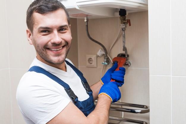 Cheerful plumber installing boiler Free Photo