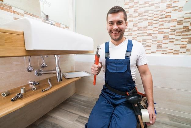 Cheerful plumber with wrench Premium Photo