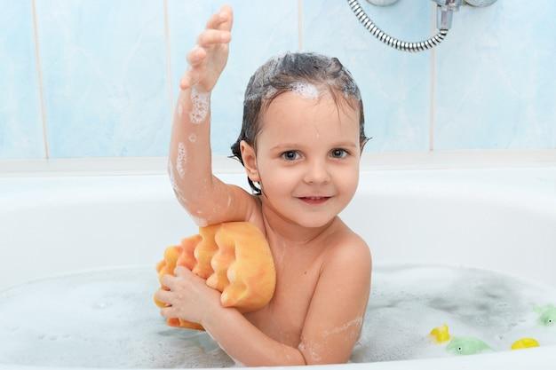 陽気な肯定的な愛らしい小さな子供が入浴し、黄色のスポンジで身を洗う 無料写真