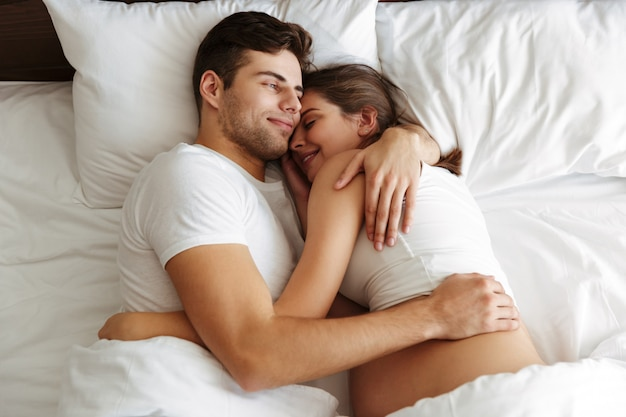 Cheerful pregnant woman lies in bed with husband Free Photo