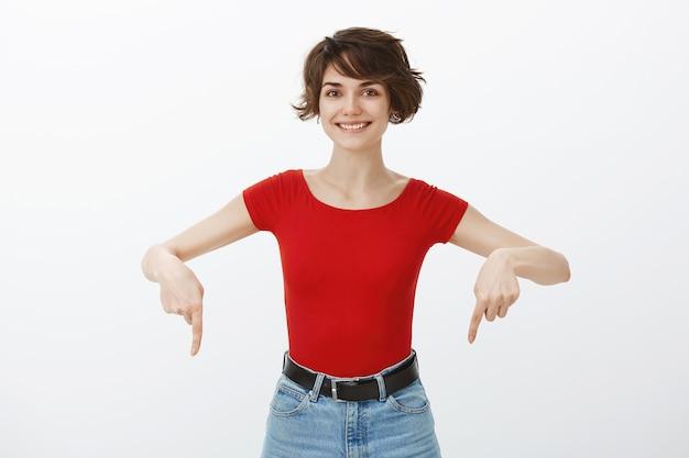 발표에서 아래로 손가락을 가리키는 명랑 예쁜 갈색 머리 여자 무료 사진