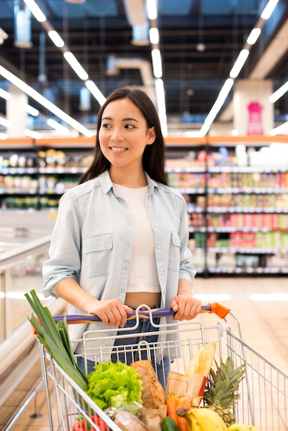 Cheerful pretty female with shopping cart at supermarket Free Photo