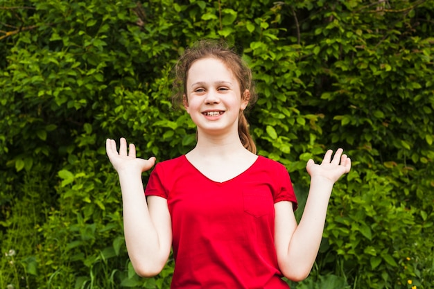 Cheerful pretty girl standing in park and gesturing Free Photo